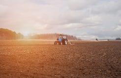 In de vroege, de lenteochtend, wegens het hout stijgt de heldere zon De tractor gaat en trekt een ploeg, die een gebied ploegen v Royalty-vrije Stock Foto's