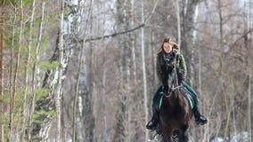 De vroege Lente Een glimlachende vrouw die een paard in het bos berijden stock videobeelden