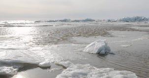 De vroege lente en dooi op zee en de beweging van water tegen de achtergrond van sneeuw en ijs stock video
