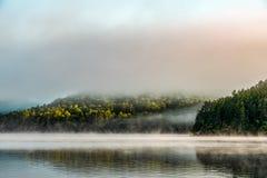 De vroege ochtendmist lanceert een klein, weerspiegelend meer royalty-vrije stock foto's