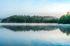 De vroege ochtendmist lanceert een klein, weerspiegelend meer stock fotografie