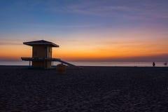 De vroege ochtendzonsopgang silhouetteert een badmeestertoren op Hollywood-Strand, Florida Stock Foto's
