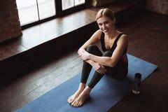 De vrolijke aantrekkelijke jonge zitting van de geschiktheidsvrouw op yogamat royalty-vrije stock afbeelding