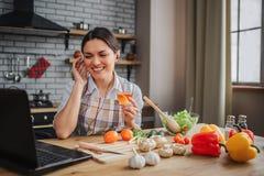 De vrolijke aardige aantrekkelijke vrouw zit bij lijst in keuken Zij glimlacht en zette draadhoofdtelefoons in oren Model kijk op stock foto