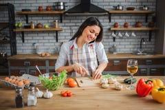 De vrolijke aardige vrouw zit bij lijst in keuken Zij sneed groene ui en bespreking op telefoon Model kijk neer Gelukkig zij royalty-vrije stock afbeelding