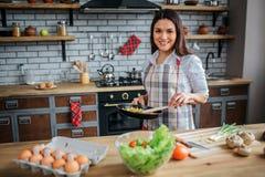 De vrolijke aardige vrouwentribune bij lijst in keuken en stelt op camera Zij houdt pan met voedsel Actief, mooi, geschiktheid, m stock afbeeldingen