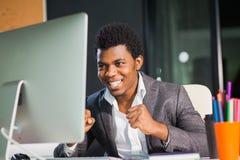 De vrolijke afro Amerikaanse mens bekijkt gelukkig monitor succesvolle ondernemer stock afbeeldingen