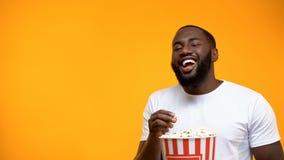 De vrolijke Afro-Amerikaanse mens popcorn eten en luid lachen die uit, komedie tonen royalty-vrije stock fotografie