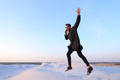 De vrolijke Arabische kerel communiceert op telefoon en stuitert lijn in m Royalty-vrije Stock Foto's