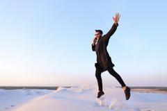 De vrolijke Arabische kerel communiceert op telefoon en stuitert lijn in m Stock Foto's