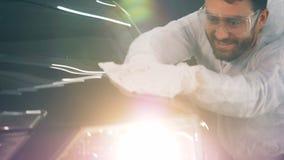 De vrolijke arbeider poetst een auto met een doek op stock videobeelden