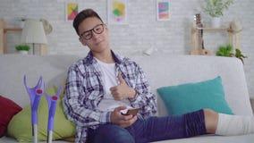 De vrolijke Aziatische jonge mens met een gebroken been in verbanden gebruikt een smartphone die camera bekijken en duimen tonen stock video