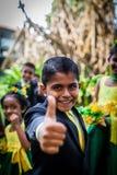 De vrolijke Aziatische jongen in een kostuum toont zijn duim tegen de achtergrond van andere kinderen royalty-vrije stock afbeelding