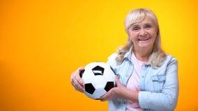 De vrolijke bal van de de holdingsvoetbal van de gepensioneerdenvrouw, sporten die, positieve houding wedden stock foto