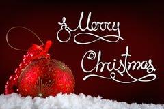 De vrolijke ballen van het Kerstmisconcept in sneeuw, het begroeten Stock Foto