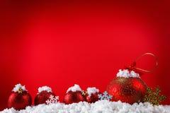 De vrolijke ballen van het Kerstmisconcept in sneeuw, het begroeten Stock Foto's