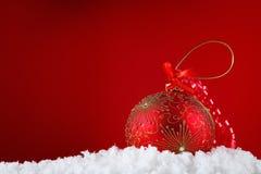 De vrolijke ballen van het Kerstmisconcept in sneeuw, het begroeten Stock Afbeeldingen