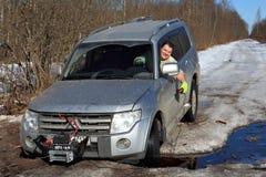 De vrolijke bestuurder trekt auto uit gat met kruk Royalty-vrije Stock Afbeeldingen