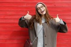 De vrolijke blije jonge vrouw status en het tonen beduimelen omhoog stock foto's