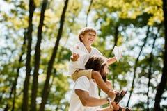 De vrolijke blonde jongen en de knappe vader gekleed in de witte t-shirts zijn in het park De jongen zit op de schouders van de v stock afbeelding