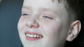 De vrolijke blonde jongen met blauwe ogen en sproeten lacht contagiously oprecht aan scheuren stock video