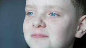 De vrolijke blonde jongen met blauwe ogen en sproeten lacht contagiously oprecht aan scheuren stock videobeelden