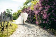 De vrolijke bruid speelt met haar huwelijkskleding terwijl het lopen langs de het bedekken weg dichtbij bloeiende liliac struiken royalty-vrije stock foto