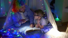 De vrolijke clown leest tijdschrift met jong geitje alvorens in magische tent met slingers bij kinderenruimte naar bed te gaan stock footage