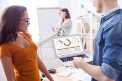 De vrolijke collega's gebruiken computer voor het werk Stock Foto
