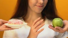 De vrolijke dame die groene appel in plaats van zoete doughnut, gewichtsverlies kiezen, sluit omhoog stock footage