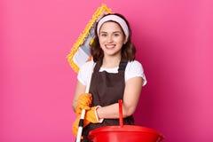De vrolijke donkerbruine vrouw houdt zwabber en emmer Meisjeswokken als meisje Glimlachende huisvrouw De vrouw maakt huis schoon  stock afbeeldingen