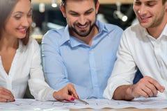 De vrolijke drie ingenieurs construeren de nieuwe bouw Royalty-vrije Stock Afbeelding
