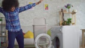 De vrolijke expressieve Afrikaanse Amerikaanse jonge vrouwenhuisvrouw met Afro-kapsel laadt kleren binnen in wasmachine stock video