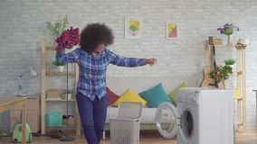 De vrolijke expressieve Afrikaanse Amerikaanse jonge vrouwenhuisvrouw met Afro-kapsel laadt kleren in klerenwasmachine, wasserij stock footage