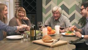 De vrolijke familie communiceert bij dinerlijst stock videobeelden
