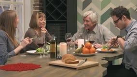 De vrolijke familie communiceert bij dinerlijst stock video