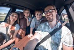 De vrolijke familie met twee kinderen gaat naar de auto royalty-vrije stock foto's