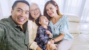 De vrolijke familie neemt thuis een groepsbeeld royalty-vrije stock afbeelding