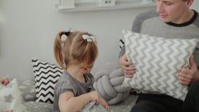 De vrolijke familie werpt hoofdkussens in elkaar in de Nieuwjaars ruimte stock video