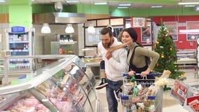 De vrolijke gelukkige familie maakt aankopen in de opslag voor de Kerstmisvakantie stock video