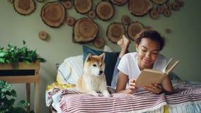 De vrolijke gemengde rastiener leest boek genietend van literatuur dan strijkend haar hond van shibainu dichtbij liggend op bed stock videobeelden