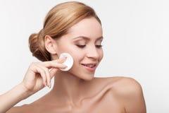De vrolijke gezonde vrouw maakt haar gezicht schoon Royalty-vrije Stock Foto