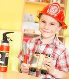 De vrolijke glimlachende jongen met speelgoed en verrekijkers in van hem dient een brandkostuum in Stock Afbeeldingen