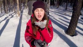 De vrolijke glimlachende positieve vrouwelijke wandelaar blaast de sneeuw van de palmen die selfie nemen stock video