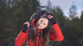 De vrolijke, glimlachende wandelaar stijgt haar hoed op Reiziger, Wandelaar positief portret in de winter bos Wandeling, liefde,  stock footage