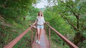 De vrolijke grappige jonge vrouw met licht blond haar loopt langs lange ijzerbrug over canioncanion, de broodjes van het toeriste stock videobeelden