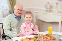 De vrolijke grootouder heeft lunch met een kind stock foto