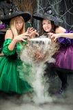De vrolijke heksen koken een drankje voor Halloween Stock Afbeelding