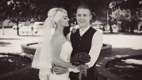 De vrolijke jonge bruid glimlacht wanneer zij zich met haar echtgenoot bevindt Gehuwd paar Echtgenoot en vrouw Close-up Rebecca 3 stock foto's