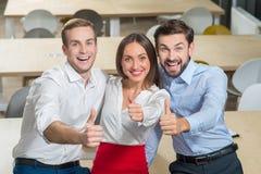 De vrolijke jonge collega's drukken positieve emoties uit Stock Fotografie
